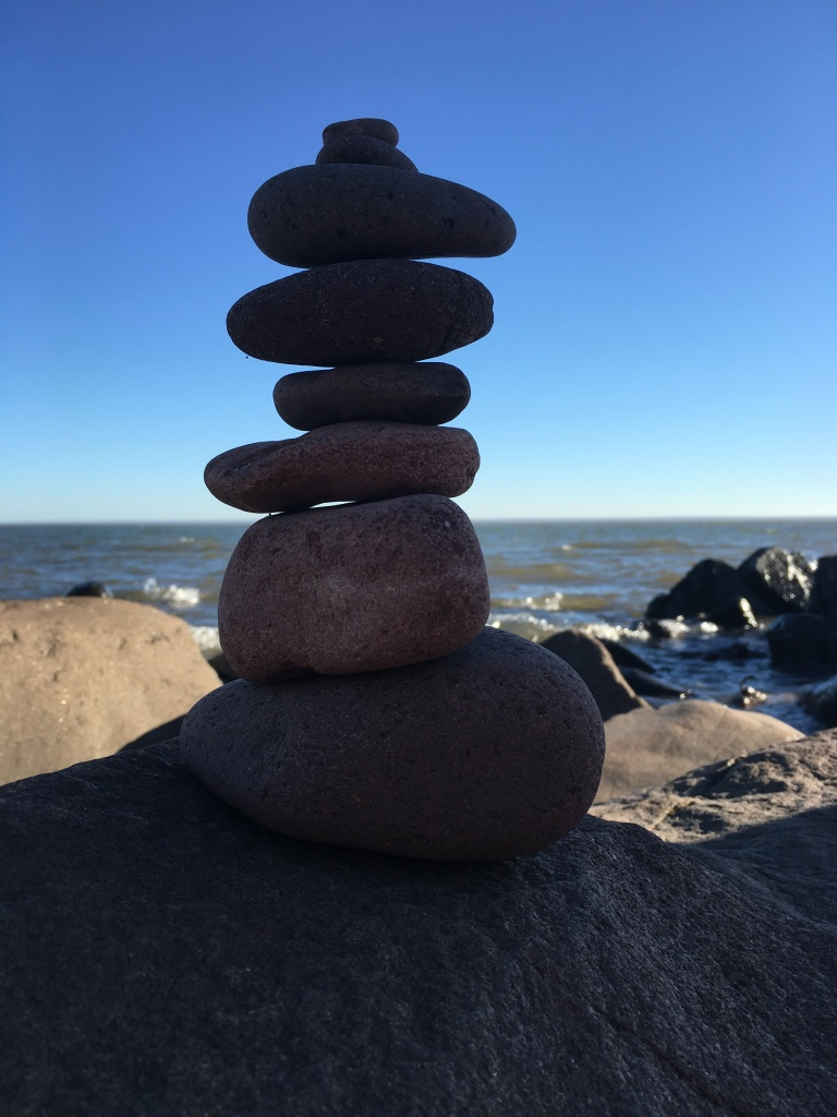 stack of rocks on the lakeshore with blue sky