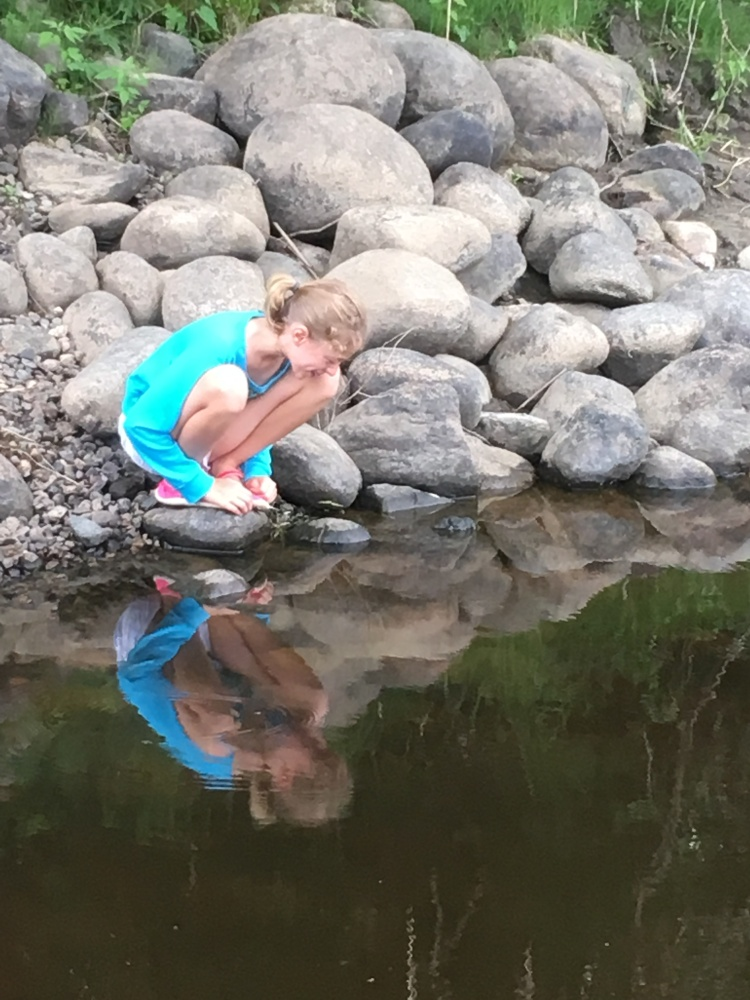 Girl looking at her reflection in a lake of water